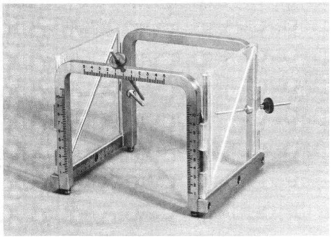 "Figure 1 — Modified LEKSELL frame with removeable plexiglass side plates. Embedded aluminum rods are set in a ""Z"" pattern. The oblique bars are used to determine the level of the C.T. slice with"